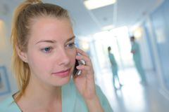 Portrait female nurse using cell phone in hospital Royalty Free Stock Photography