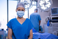 Portrait of female nurse wearing surgical mask in operation theater Stock Photos