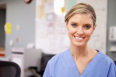 Portrait Of Female Nurse Working At Nurses Station Stock Photo