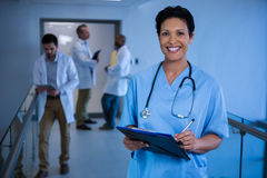 Portrait of female nurse writing in clipboard in corridor Stock Photo