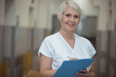 Portrait of female nurse writing on clipboard in corridor. At hospital Stock Photo