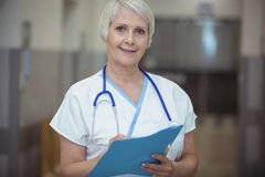 Portrait of female nurse writing on clipboard in corridor. At hospital Stock Image