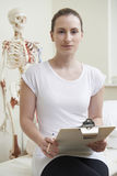 Portrait Of Female Osteopath In Consulting Room Stock Photos
