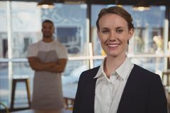 Portrait of female owner with waiter in background at cafe royalty free stock photos