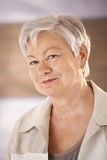 Portrait of female pensioner. Closeup portrait of female pensioner with white hair, looking at camera, smiling Royalty Free Stock Photos