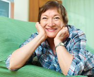 Portrait of female pensioner woman relaxing in couch Stock Photos