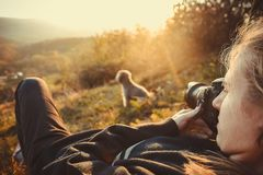 Portrait of a female photographer. Shooting a dog in nature. Catch in the sunset Royalty Free Stock Photo