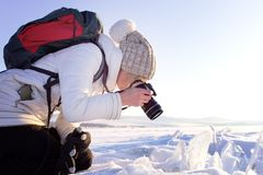 Portrait of female photographer shooting winter landscape next to the frozen lake Baikal. Winter tourism in Russia.  Stock Photos