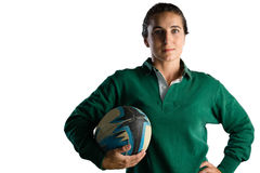 Portrait of female player with rugby ball standing with hand on hip. Against white background royalty free stock photo