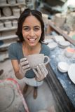 Portrait of female potter holding clay cup Royalty Free Stock Photo