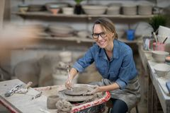 Portrait of female potter molding plate with hand tool Stock Image