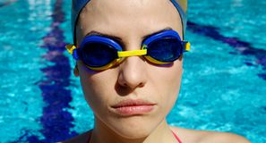 Portrait of female professional swimmer in the water. Woman swimmer in pool concentrating before competition Stock Photography