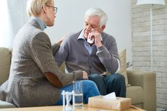 Senior Man Crying in Therapy. Portrait of female psychiatrist comforting senior men crying during therapy session, copy space stock images