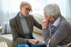 Senior Man Crying in Therapy Session. Portrait of female psychiatrist comforting senior men crying during therapy session royalty free stock image
