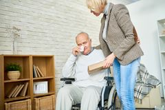 Handicapped Senior Man Crying in Therapy. Portrait of female psychiatrist consoling crying senior men in wheelchair during therapy session, copy space stock photo