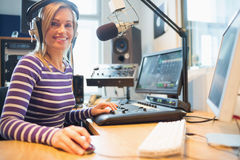 Portrait of female radio host using computer in studio Stock Image