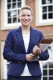 Portrait Of Female Realtor Standing Outside Residential Property Stock Photography