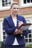 Portrait Of Female Realtor Standing Outside Residential Property stock photo