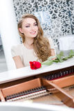 Portrait of female with red rose playing piano Stock Images