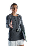 Portrait of female rugby coach extending arm for handshake. While standing against white backgrond Stock Images