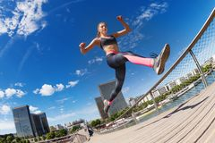 Female runner jumping while running in city Stock Photos
