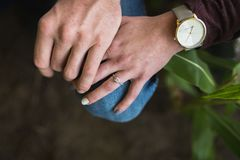 Portrait of female`s engagement ring. Couple touching hands featuring detailed shot of engagement ring in a moody setting stock images