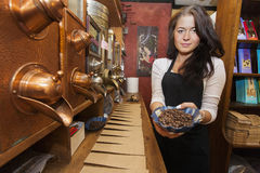 Portrait of female salesperson showing fresh coffee beans in store Royalty Free Stock Images