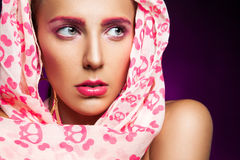 Portrait of female in scarf on purple background Royalty Free Stock Image