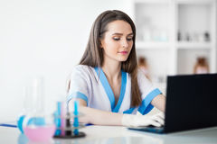 Portrait of female scientist working on laptop in chemical labor. Portrait of confident female scientist working on laptop in chemical laboratory Stock Photography