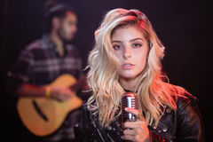 Portrait of female singer holding mic at nightclub. Portrait of young female singer holding mic at nightclub during music festival Royalty Free Stock Photography