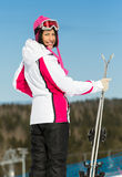 Portrait of female skier standing with skis in hands Stock Photos