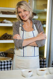 Portrait of female staff standing with arms crossed at counter Stock Photo