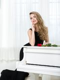 Portrait of female standing near the piano Stock Images