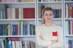 Portrait of female student in library. Portrait of happy smilling female student girl in school library Stock Image