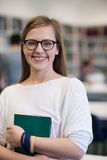 Portrait of female student in library. Portrait of happy smilling female student girl in school library bholding book Stock Image