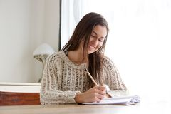 Female student sitting at desk and writing in books. Portrait of female student sitting at desk and writing in books Royalty Free Stock Photos