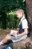 Schoolgirl teenager reading a book in a park near a tree royalty free stock photo