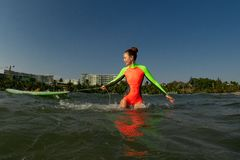 Female surfer on her surfboard in the water stock photography