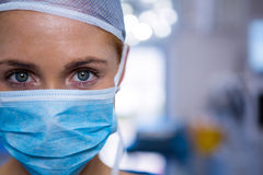 Portrait of female surgeon wearing surgical mask in operation theater. At hospital stock photo