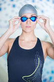 Portrait of a female swimmer. That wearing a swimming cap and goggles and preparing to jump into swimming pool. Sporty woman Stock Image