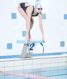 Portrait of a female swimmer. That wearing a swimming cap and goggles and preparing to jump into swimming pool. Sporty woman Stock Photography
