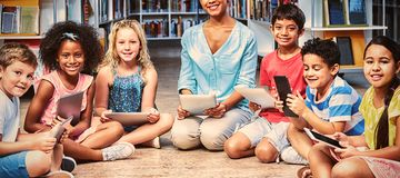 Teacher with children holding digital tablets stock photos