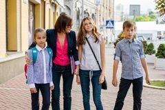 Portrait of female teacher with group student standing outside school.  Royalty Free Stock Image