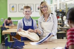 Portrait Of Female Teacher Helping Male High School Student Building Guitar In Woodwork Lesson royalty free stock photography