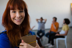 Portrait of female teacher holding clipboard with students talking in background. At art class stock photography
