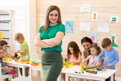 Portrait of female teacher smiling at camera and kids studying at preschool royalty free stock image