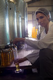 Portrait of female technician examining olive oil royalty free stock photos