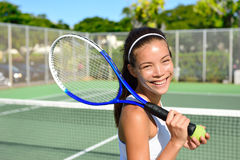 Portrait of female tennis player after playing. Portrait of female tennis player holding tennis racket after playing at game outside on hard court in summer. Fit Royalty Free Stock Photography