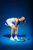 Portrait of female tennis player with racket and ball aside in studio Royalty Free Stock Photography