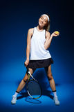 Portrait of female tennis player with racket and ball in hand posing in studio Stock Photo